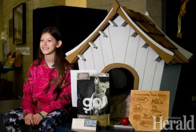 Grade 7 student Vivian Moore from G.S. Lakie Middle School sits next to the dog house that her and her classmates constructed to give back to local families in the community. Herald photo by Greg Bobinec